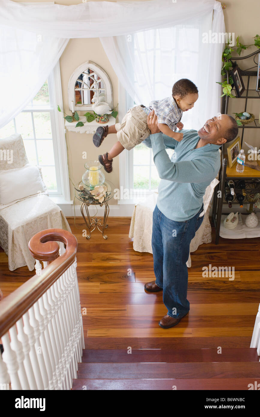 A grandfather lifting his grandson in the air - Stock Image
