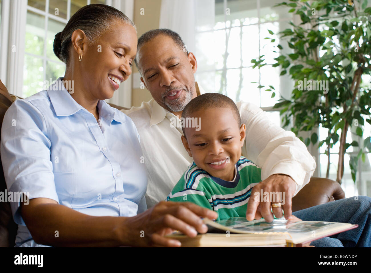 Grandparents and their grandson looking at a photo album - Stock Image