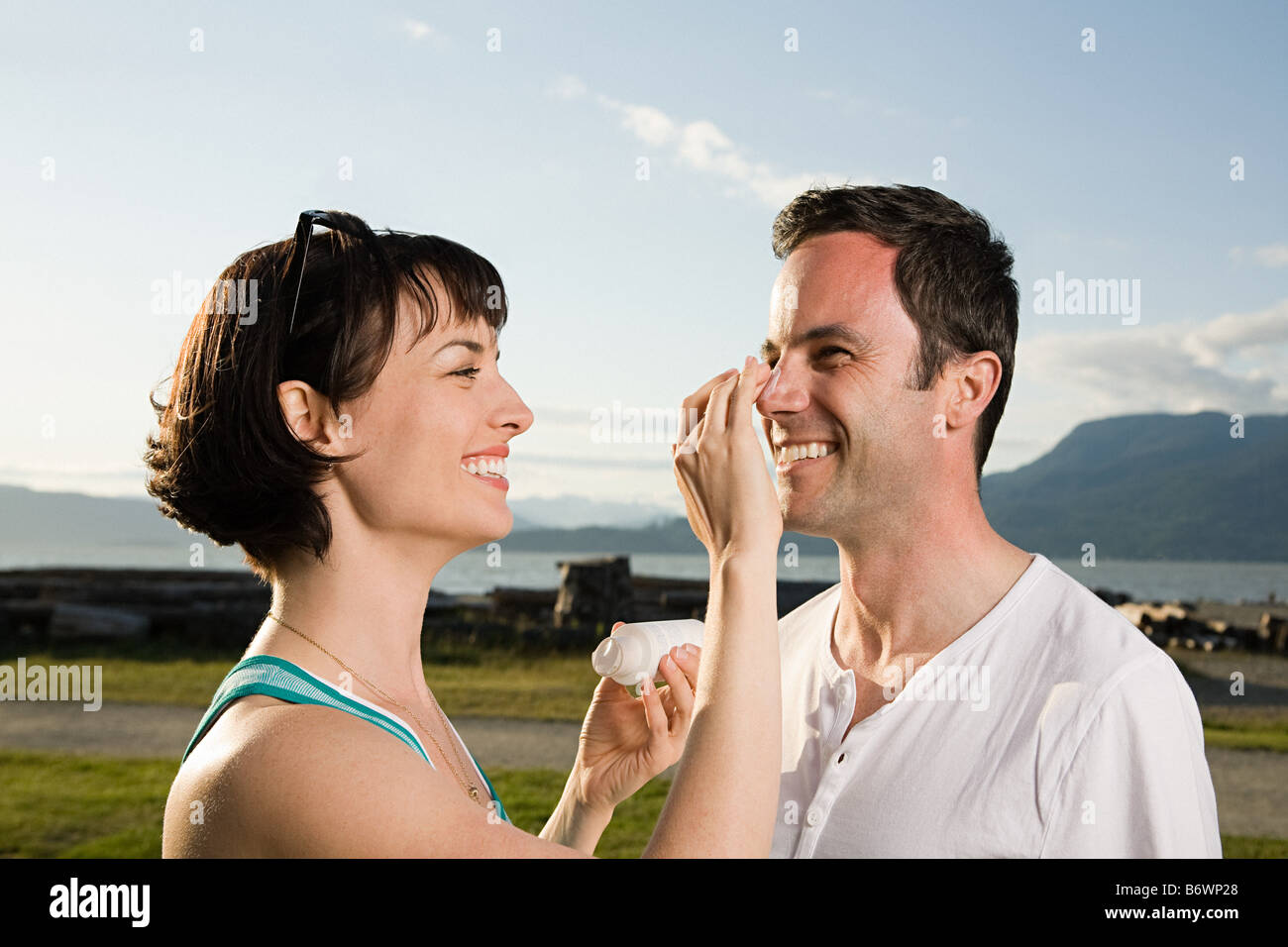 Couple applying suntan lotion - Stock Image
