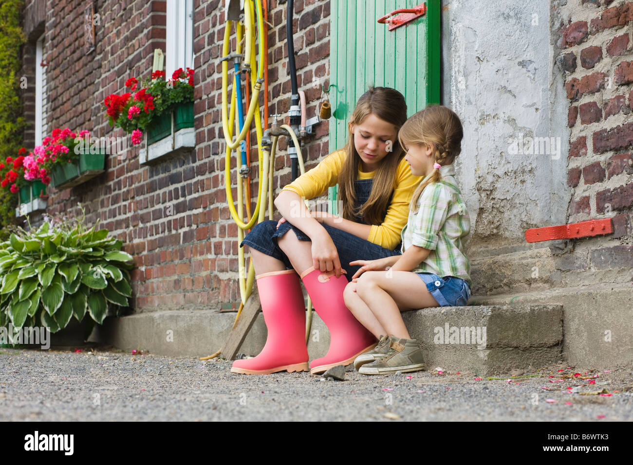Sisters sitting on a step - Stock Image