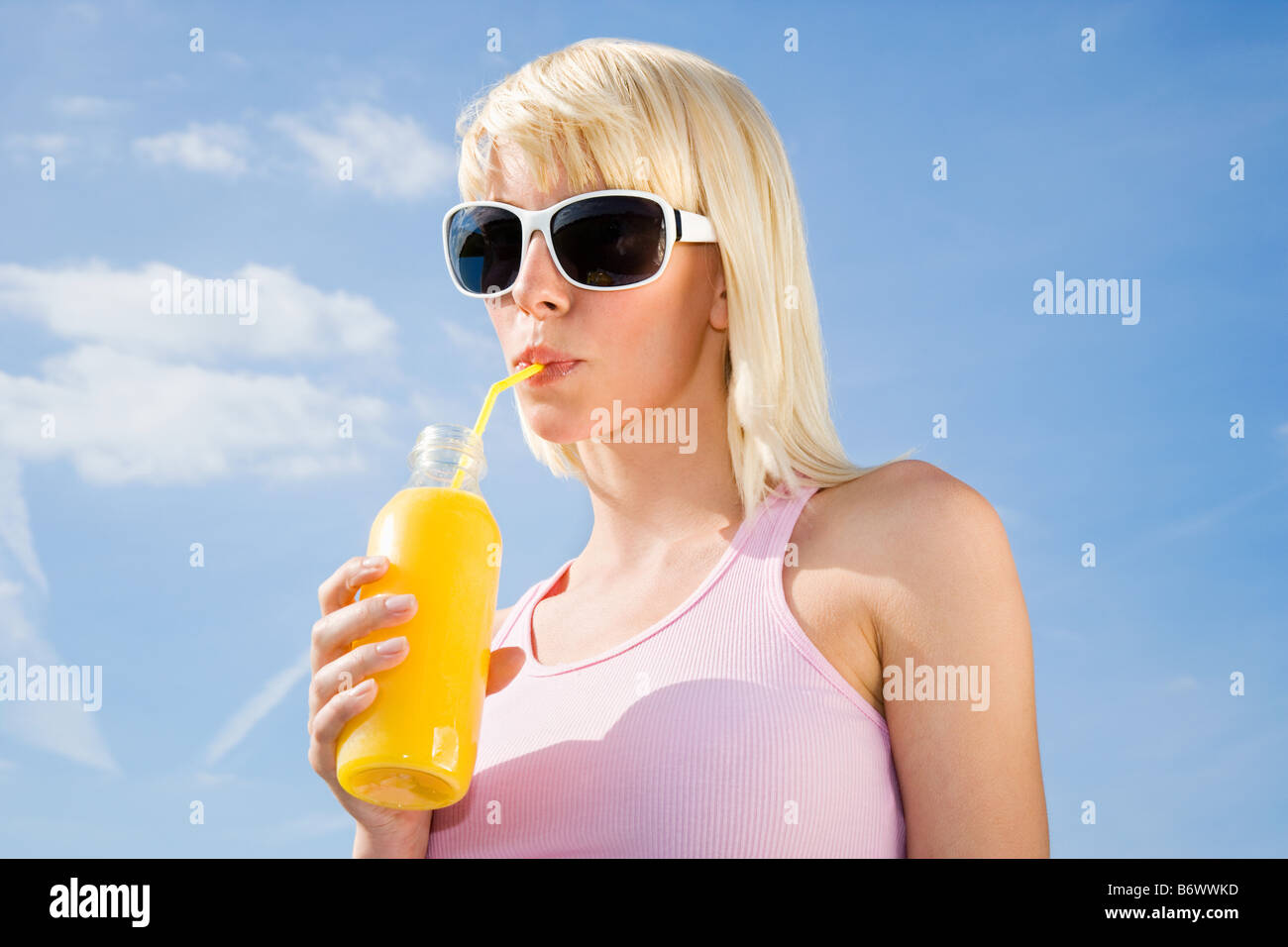 Woman drinking orange juice - Stock Image