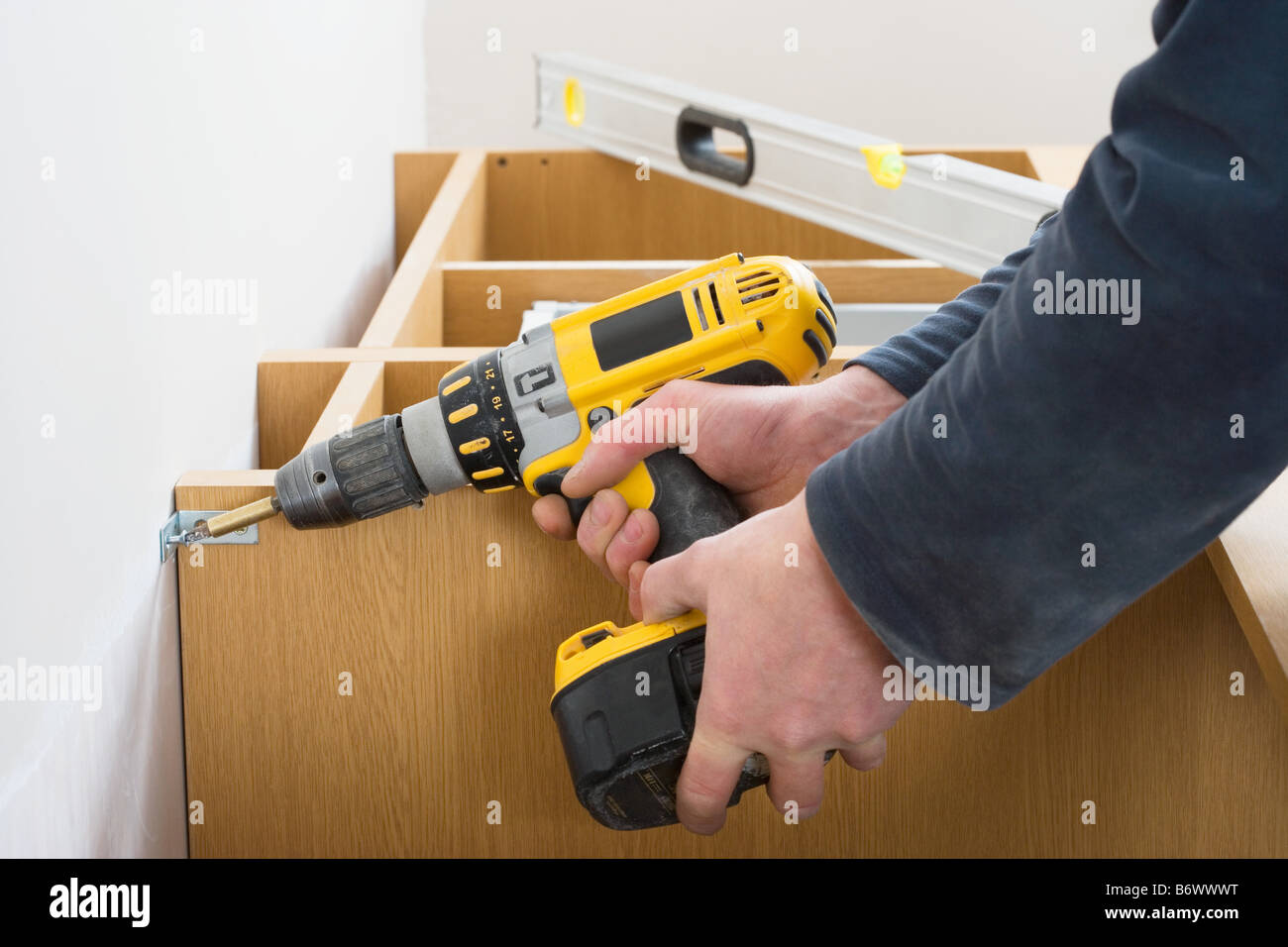 Man screwing a shelf to a wall - Stock Image