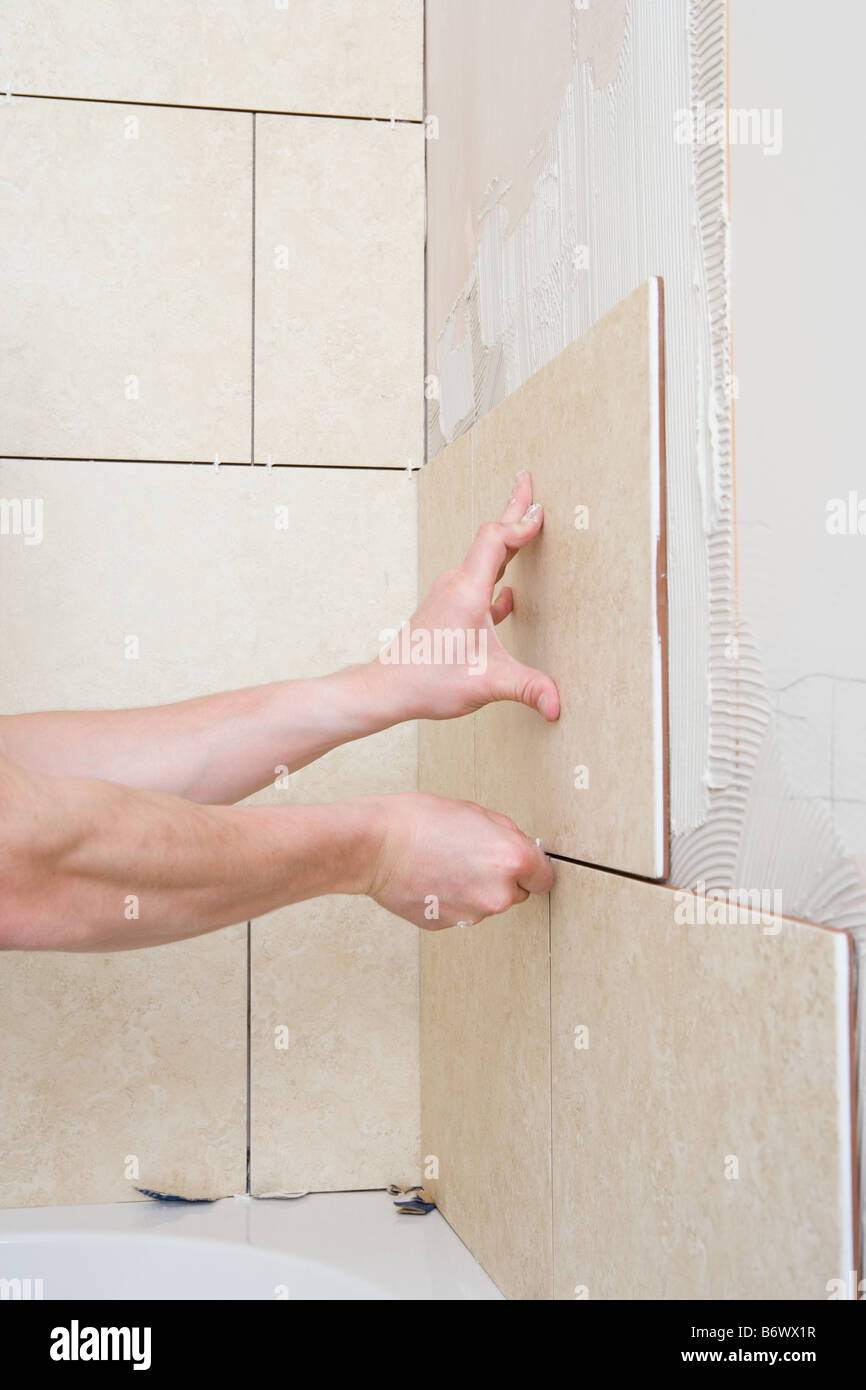 A decorator placing tiles on a wall - Stock Image