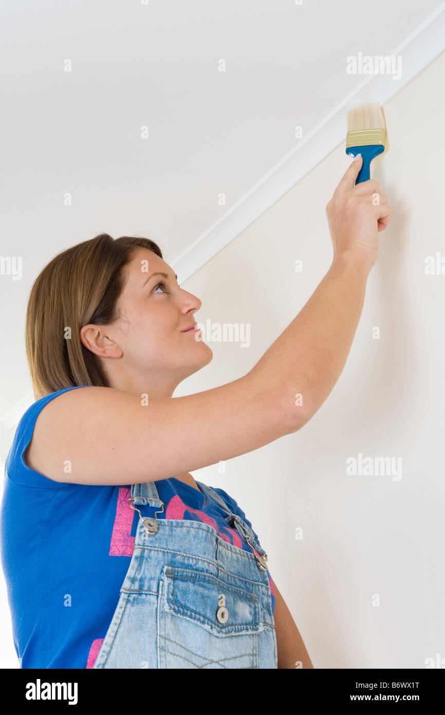 A decorator painting coving - Stock Image