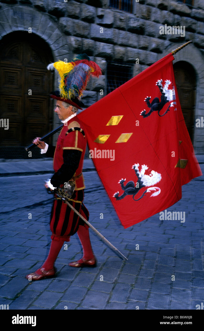 A Florentine man in traditional civic uniform carrying a flag emblazoned with symbolism of heraldry during a parade - Stock Image