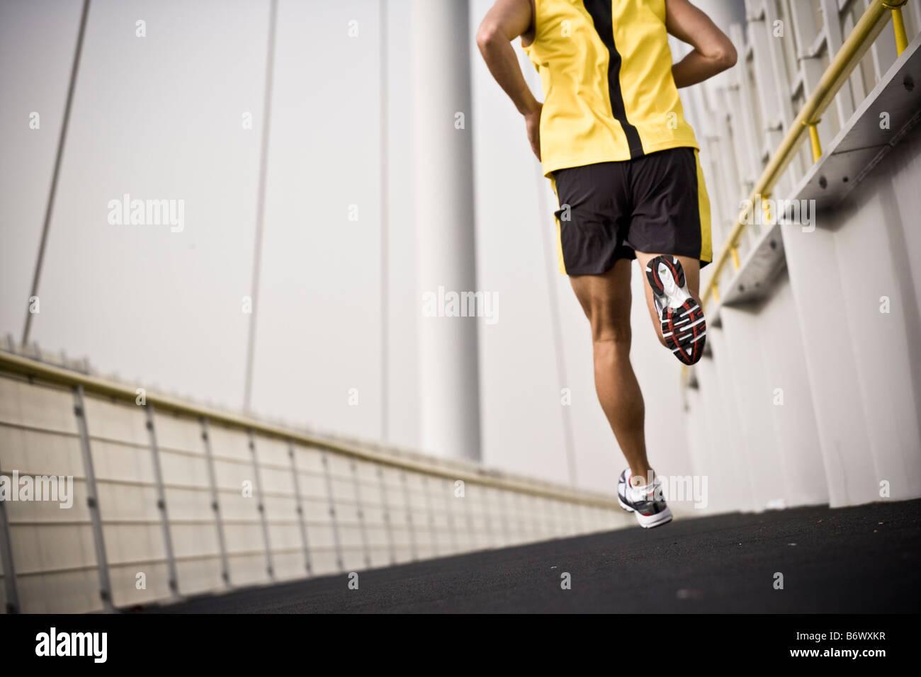 Man running across a bridge. - Stock Image