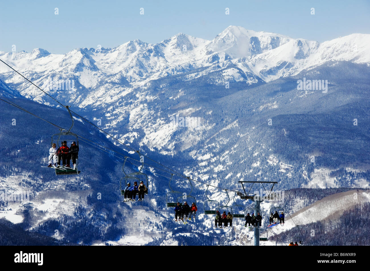 USA, Colorado, Vail Ski Resort. Skiers being carried on a chair lift in Vail back bowls - Stock Image