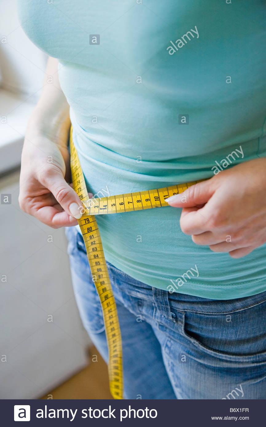 Woman measuring her belly - Stock Image