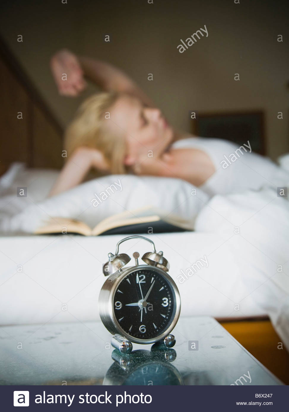 Woman in her bed with clock and book - Stock Image