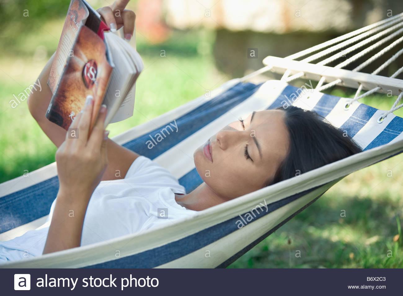 Woman reading in hammock - Stock Image