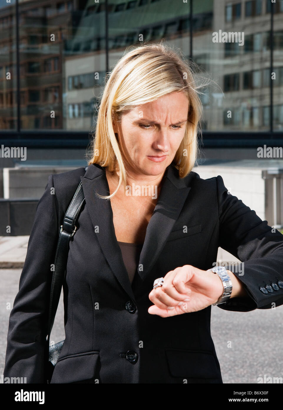 Businesswoman looks at her watch - Stock Image