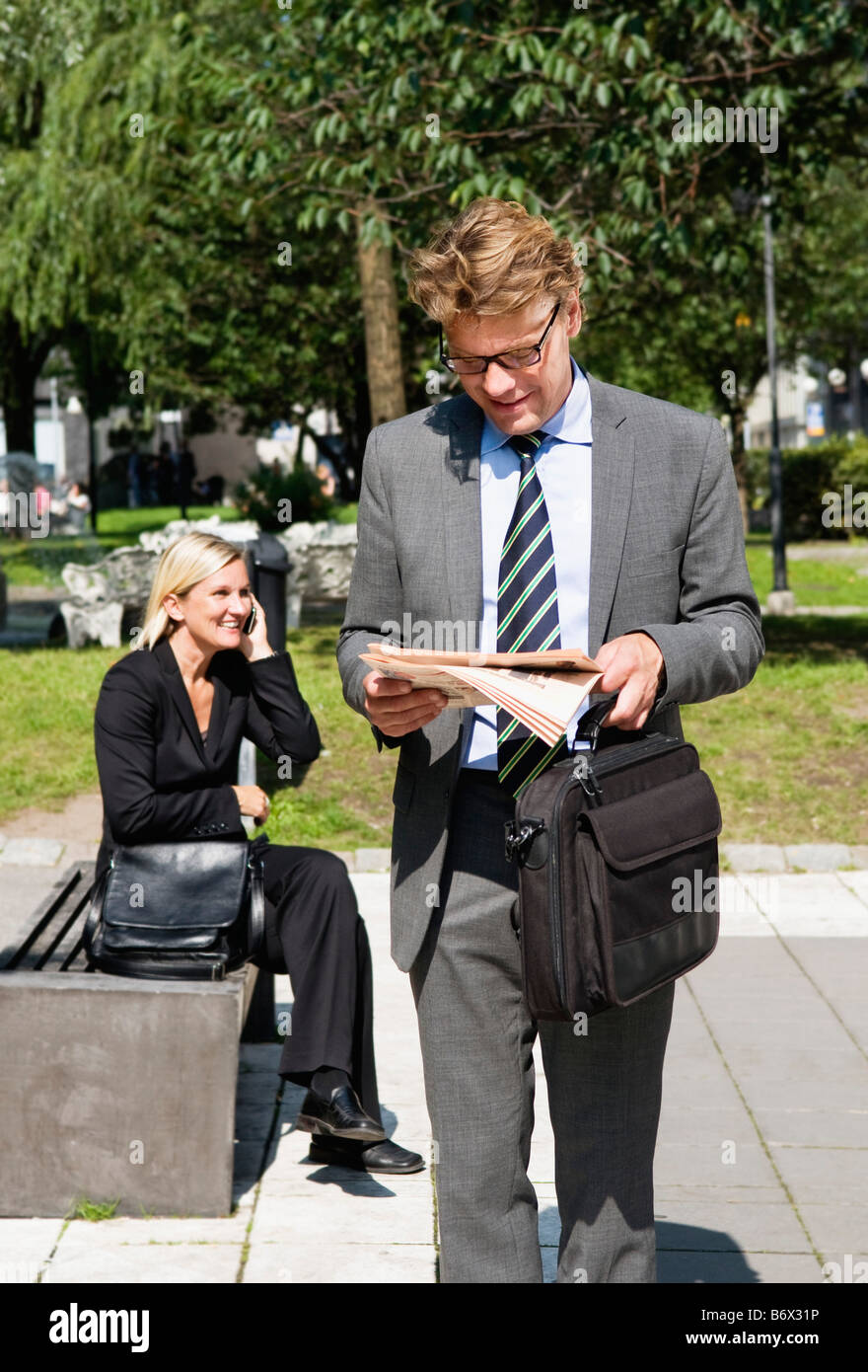 Businessman and businesswoman in park Stock Photo
