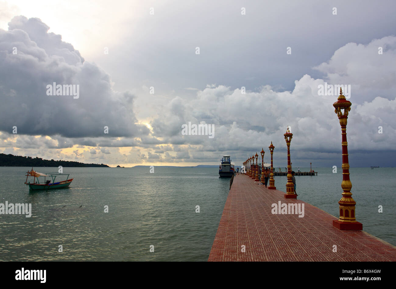 Red jetty with boat in Sihanoukville at a stormy sunset with thunder clouds, Cambodia, South East Asia - Stock Image