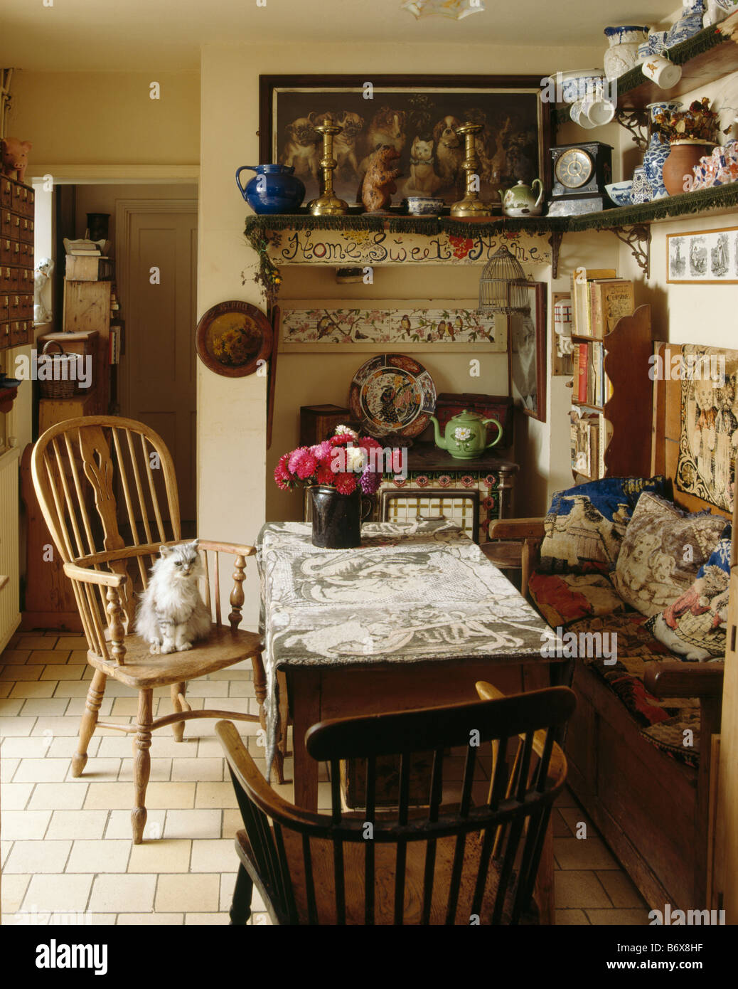 Cat On Antique Windsor Chair In Cluttered Cottage Dining Room With Tapestry  Cushions On Wooden Settle And Crockery On Shelves