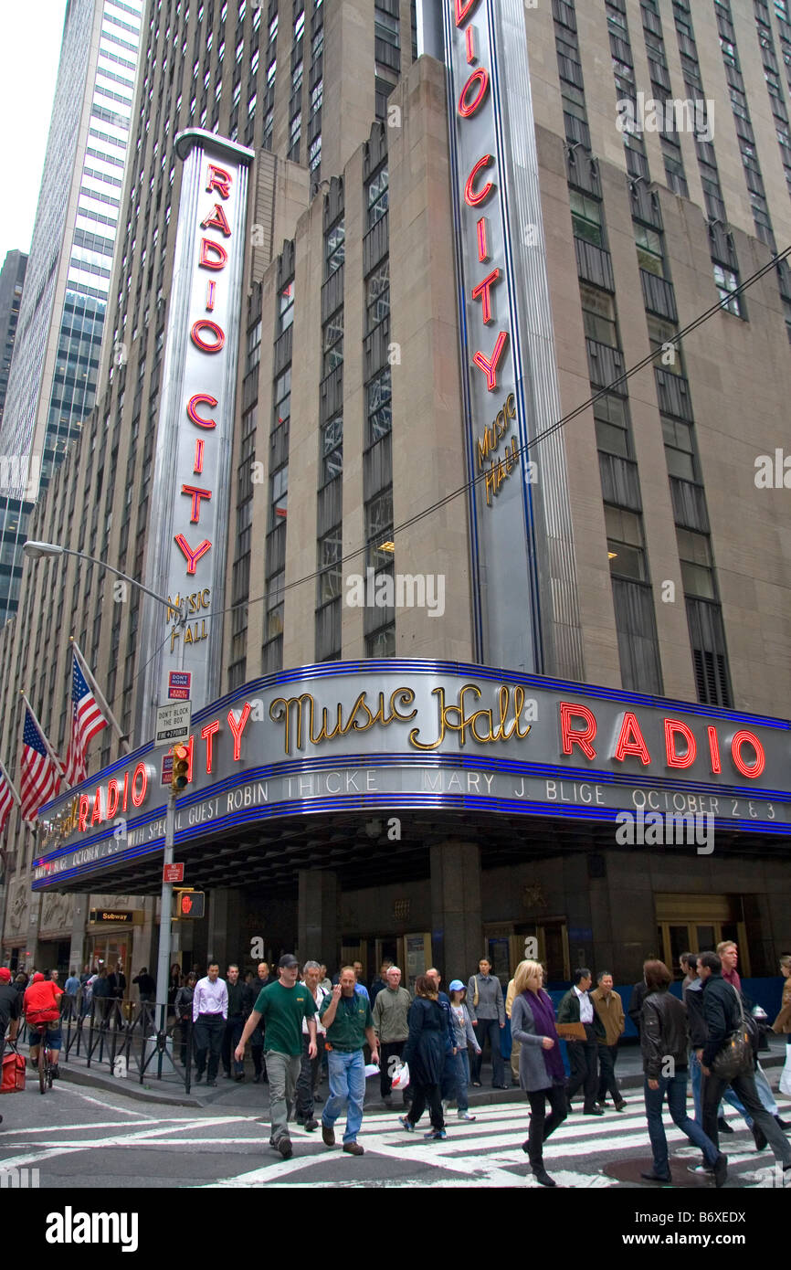Pedestrians cross the street in front of Radio City Music Hall located in Rockefeller Center Manhattan New York - Stock Image