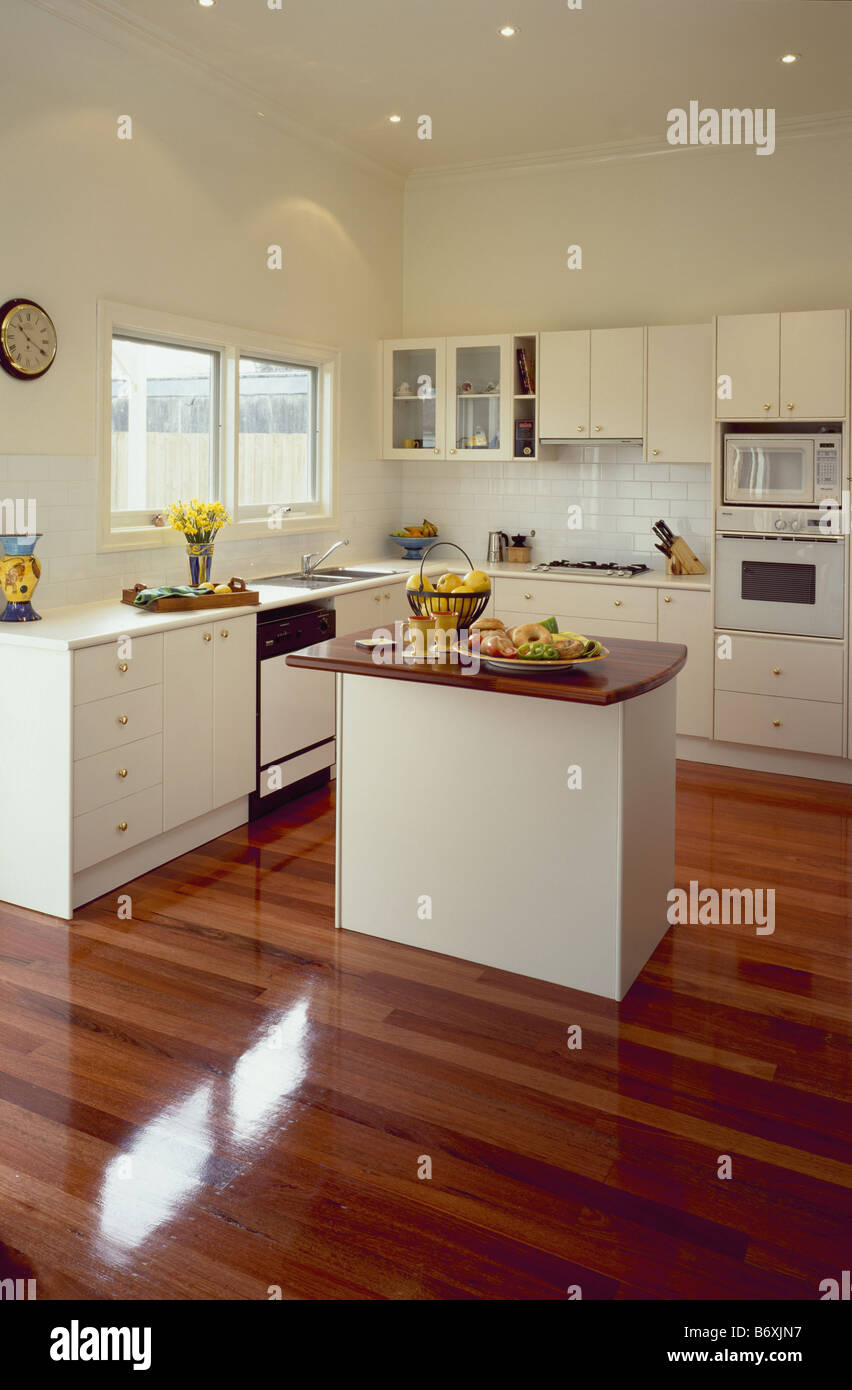Varnished wooden flooring in modern white kitchen with recessed lighting and island unit - Stock Image