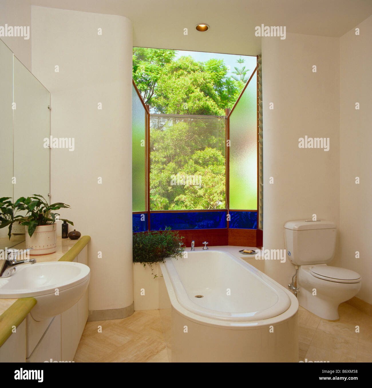 Freestanding bath in front of window with blue stained glass detail ...