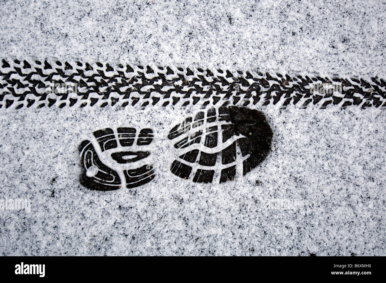 tyre and trainer tracks left in the snow by runners and cyclists defying the weather. - Stock Image