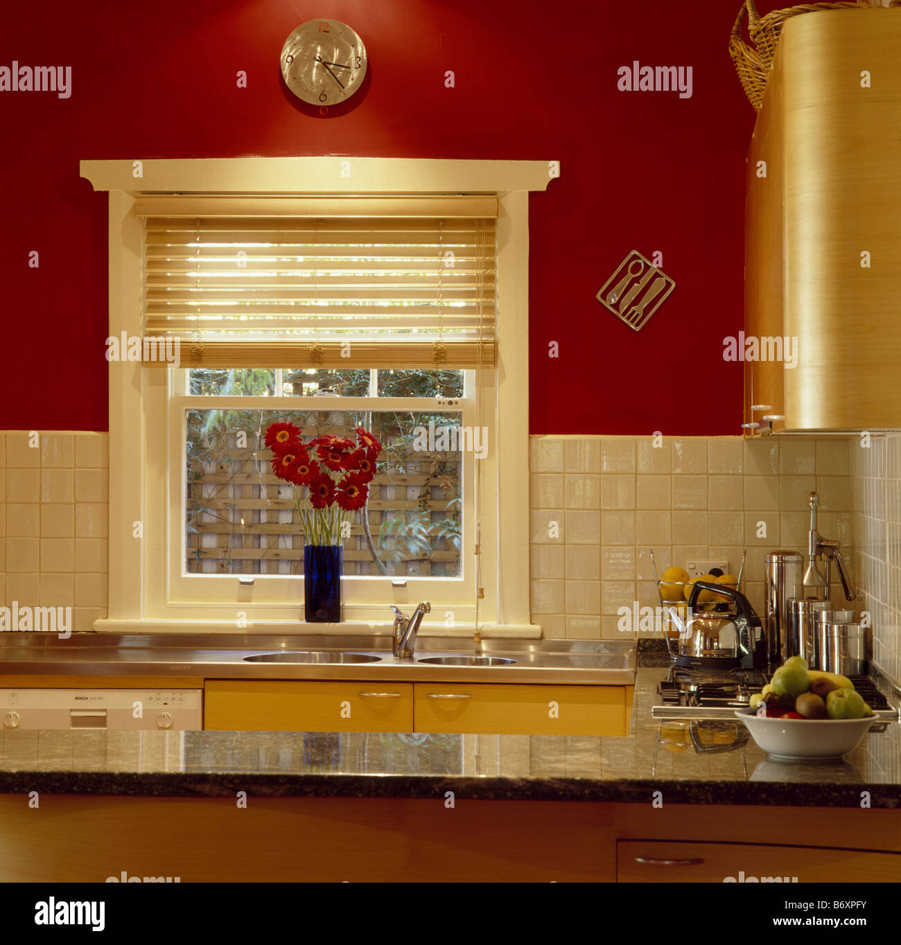 Cream pinoleum blind on window in red kitchen with cream ...