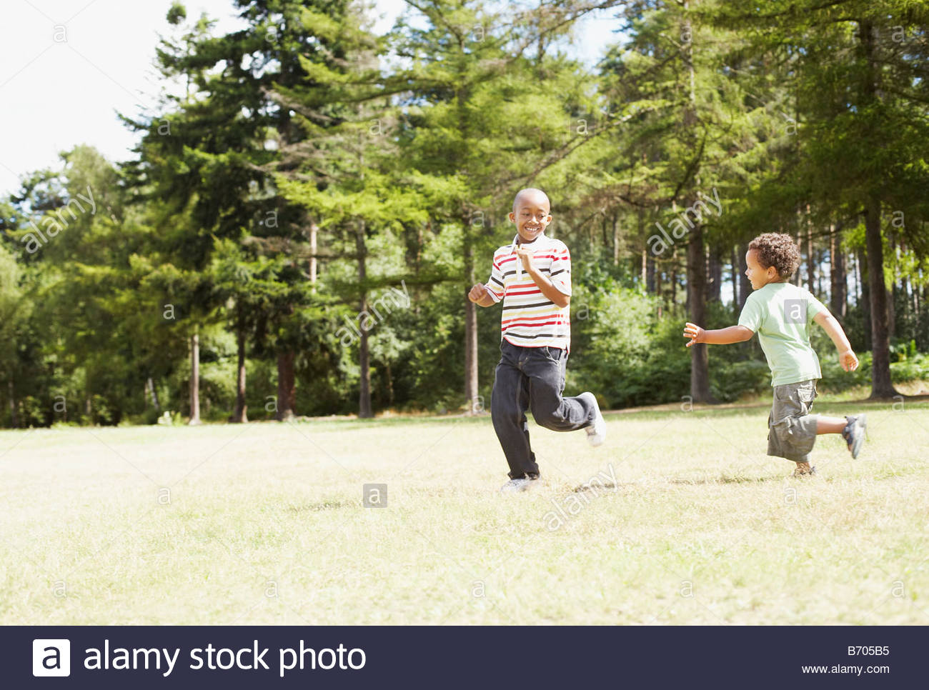 Brothers running together in park - Stock Image