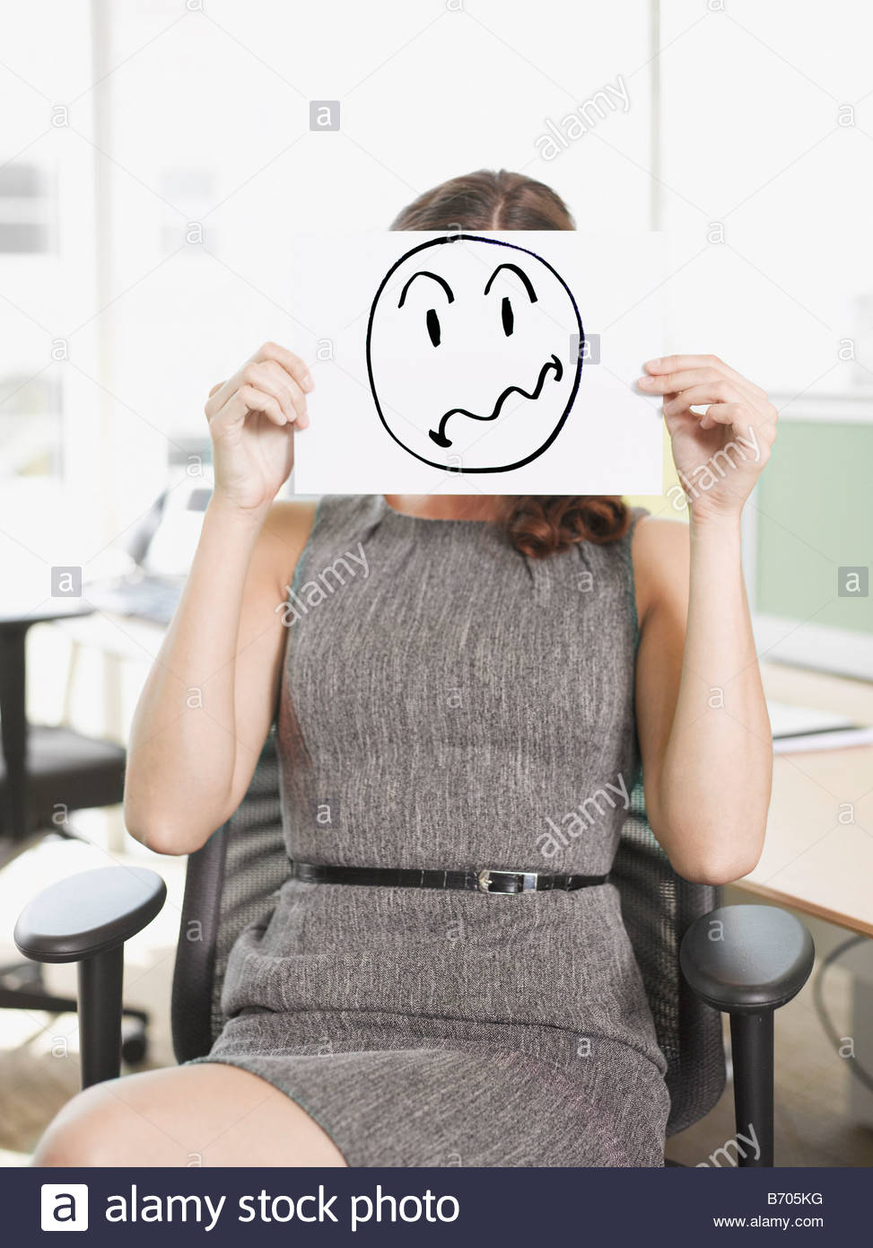 Businesswoman holding picture of frustrated face - Stock Image