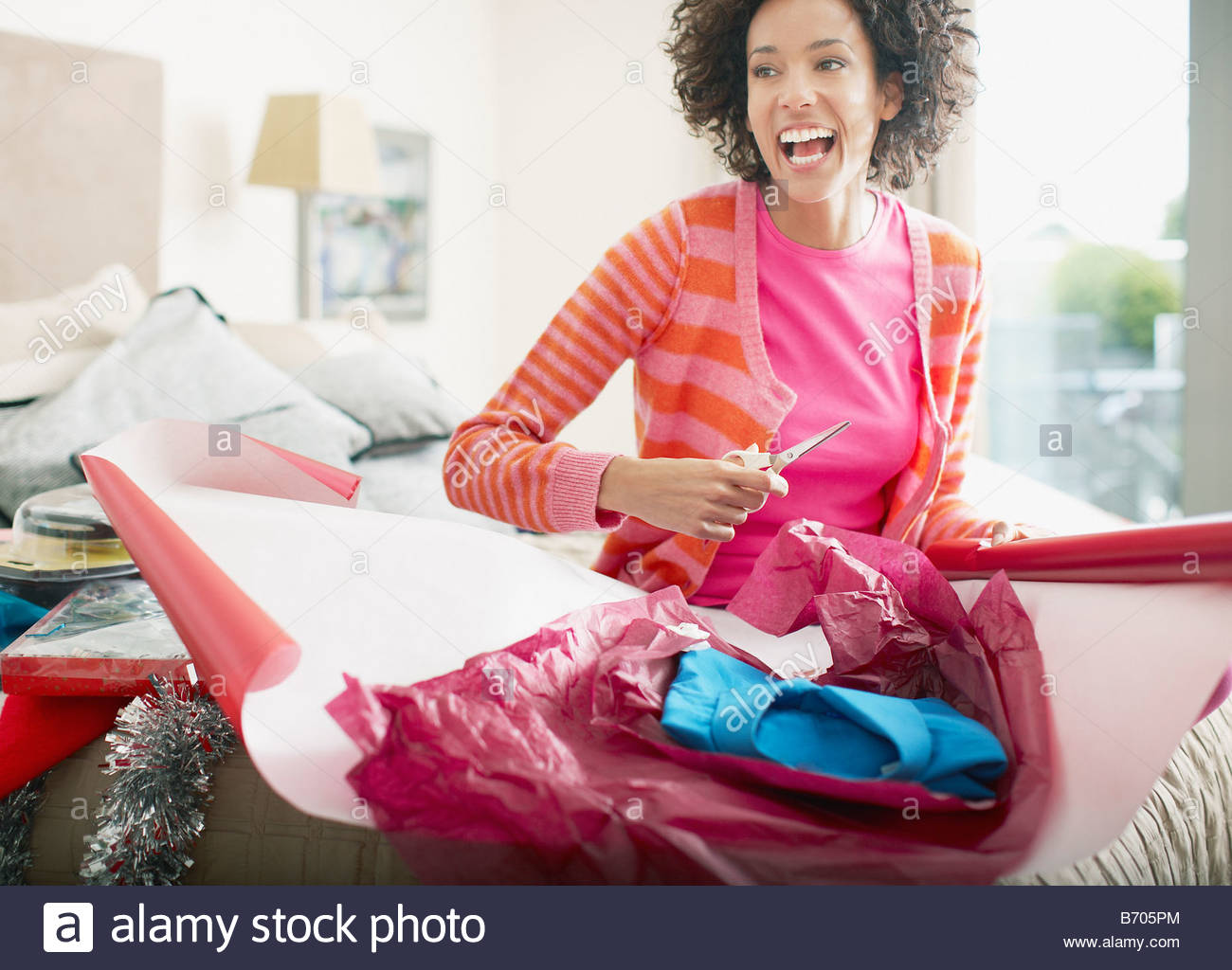 Woman wrapping Christmas gift - Stock Image