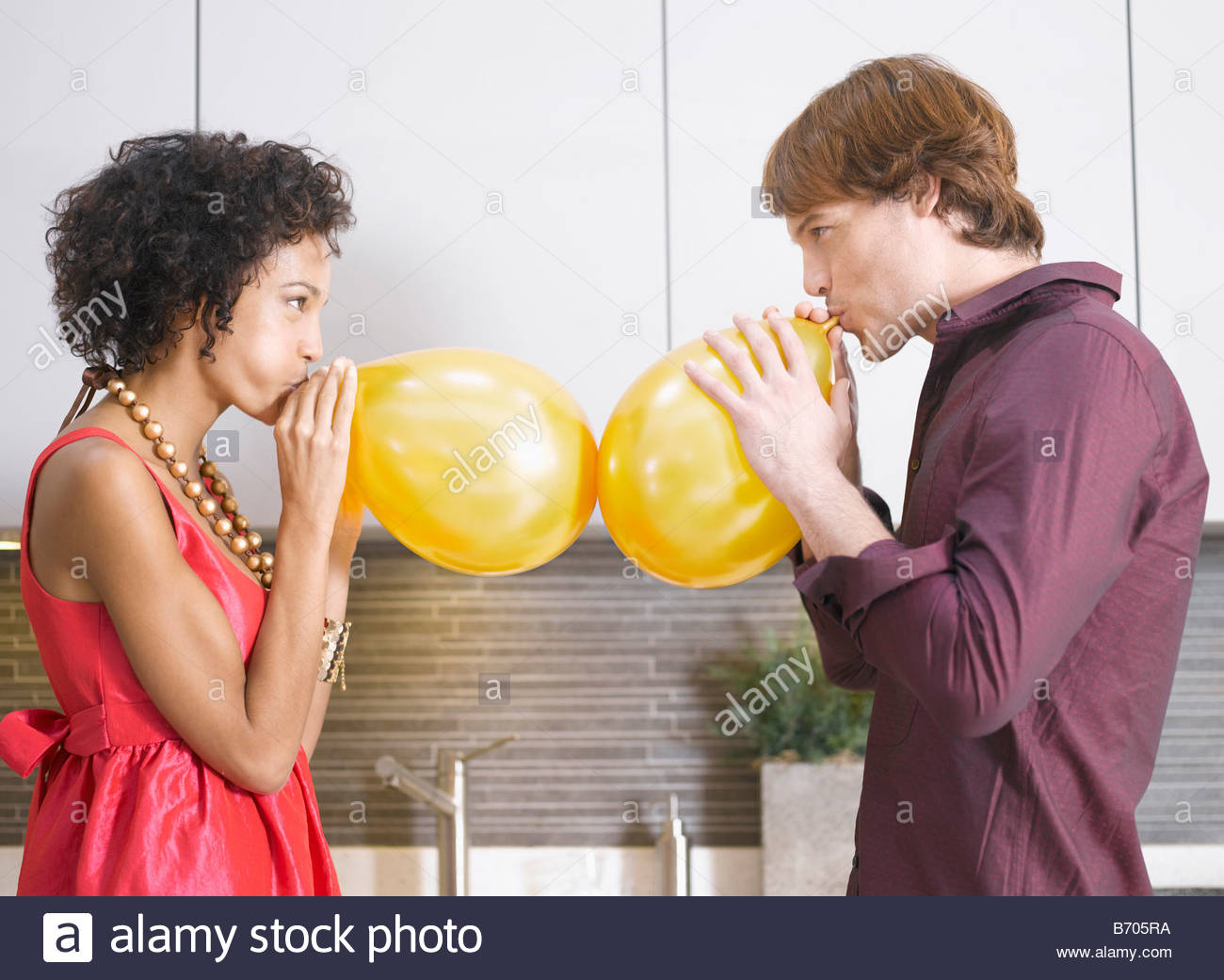 Couple blowing up balloons - Stock Image