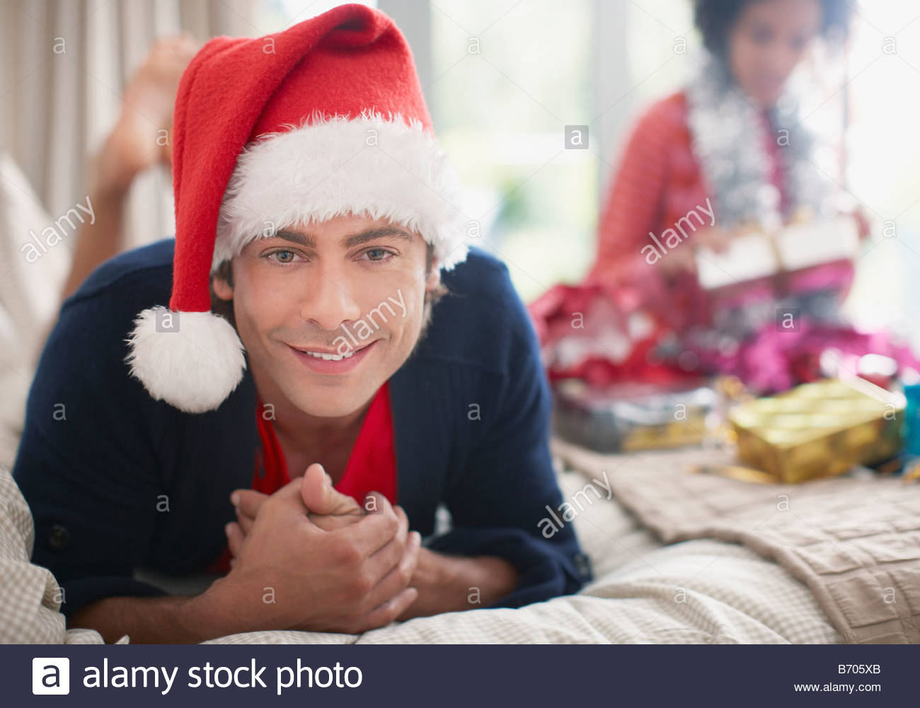 Man laying on bed in Santa hat - Stock Image