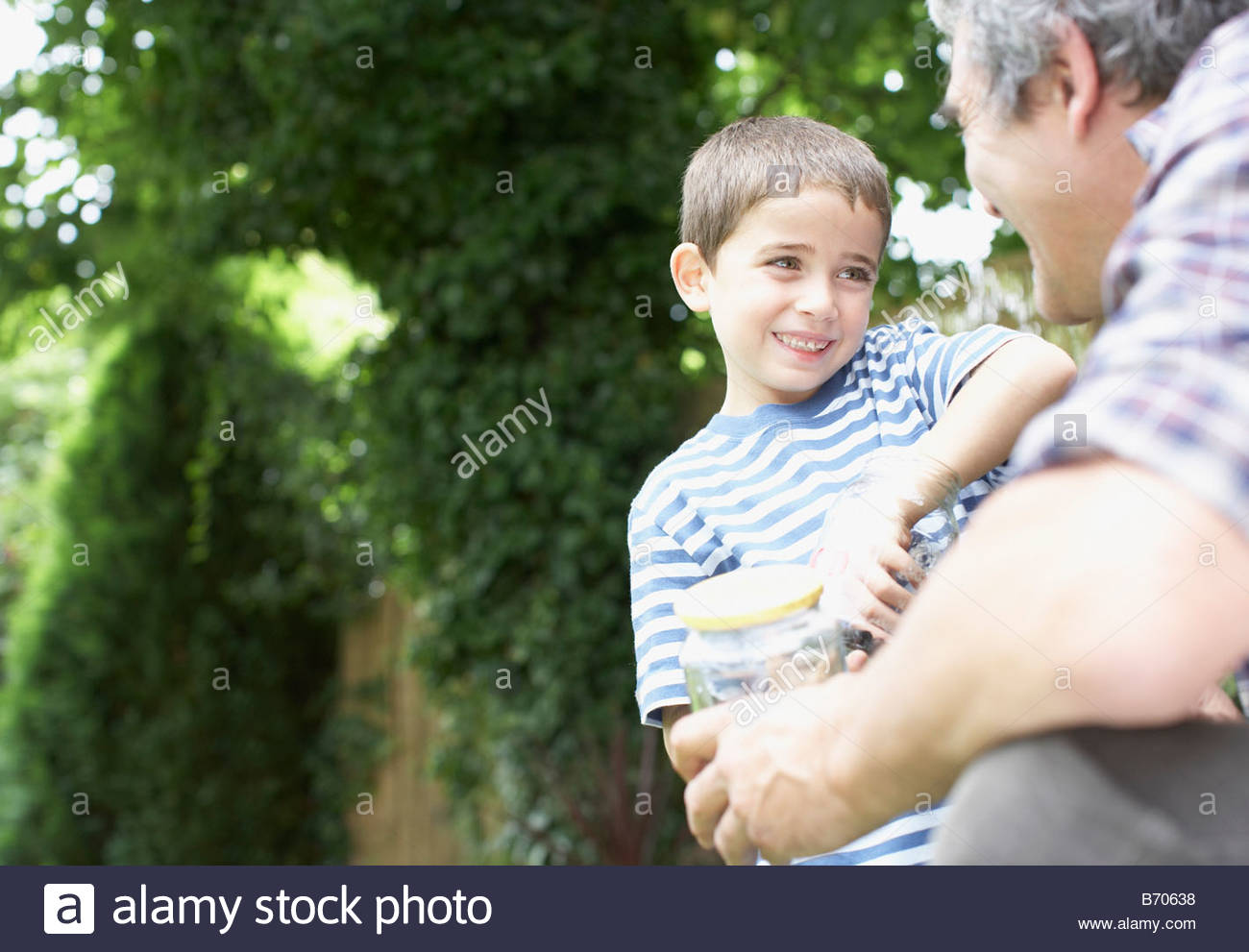 Grandfather and grandson holding insect jar - Stock Image