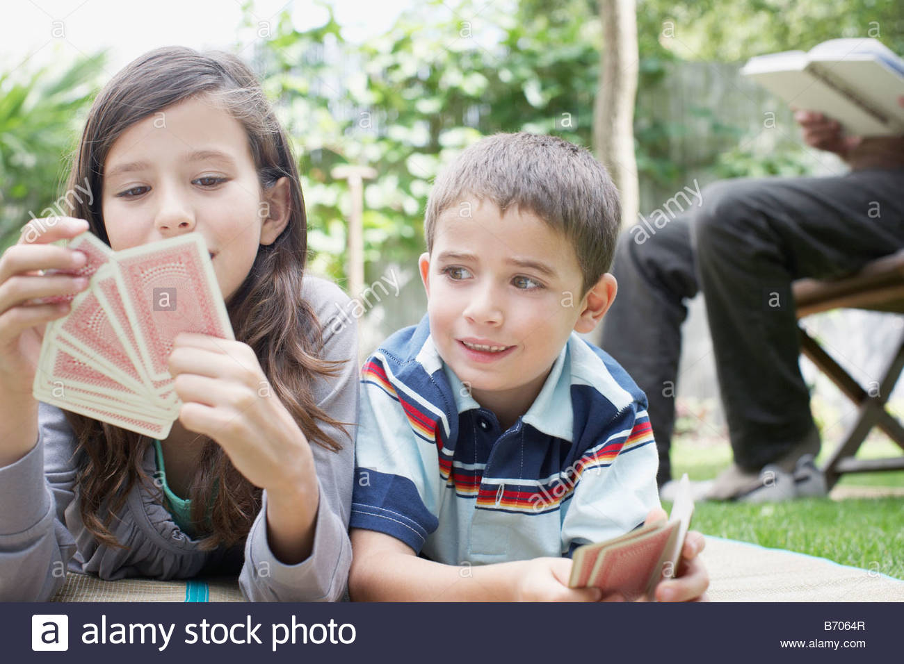 Brother and sister playing cards outdoors - Stock Image