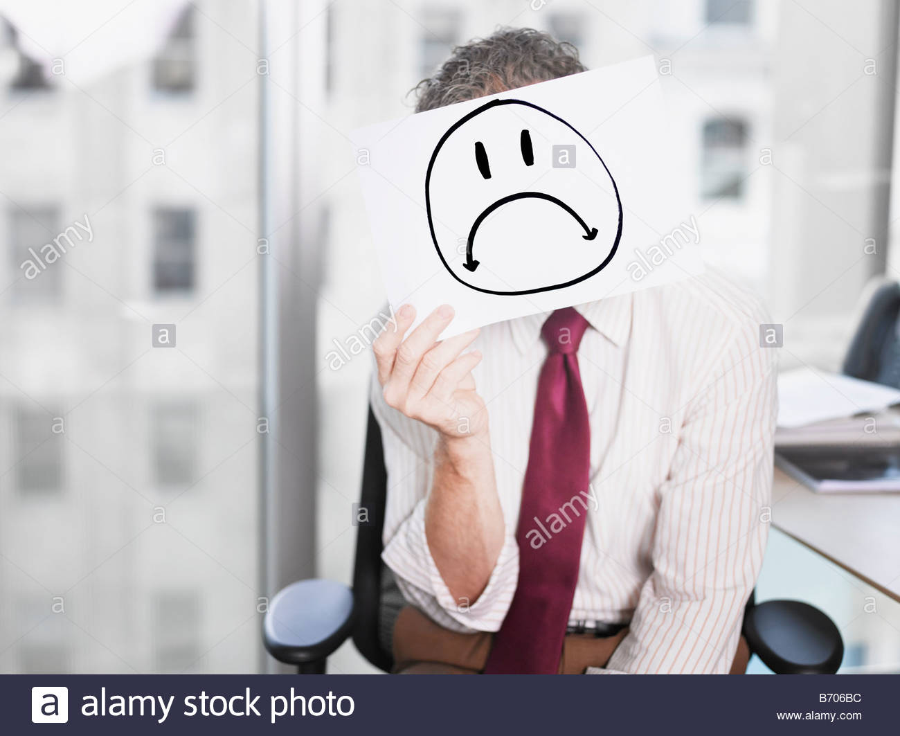 Businessman holding picture of sad face - Stock Image