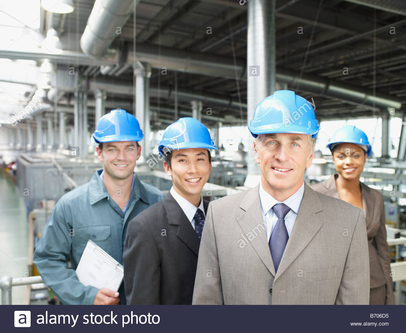 Businesspeople wearing hard-hats in factory Stock Photo