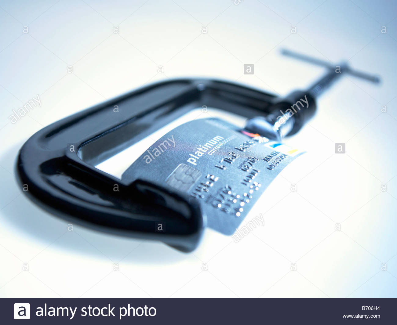 Credit card being squeezed in vice - Stock Image