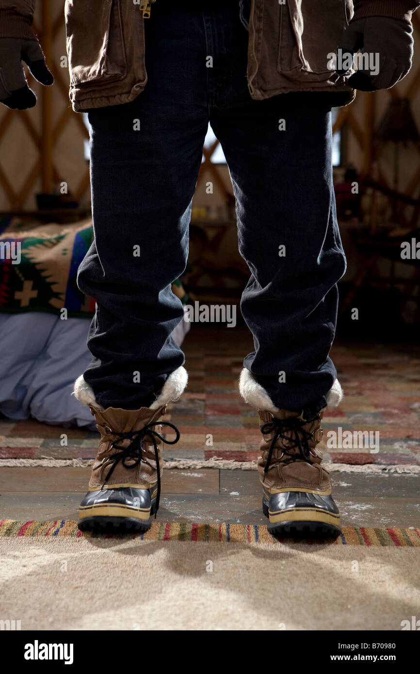 Close up of feet in boots in sparse yurt, Whitefish, Montana