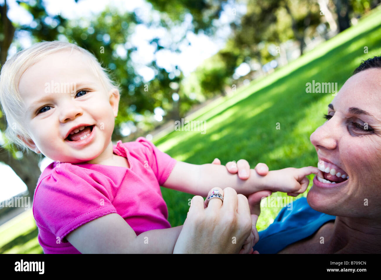 One year old girl and mom playing in the park. - Stock Image