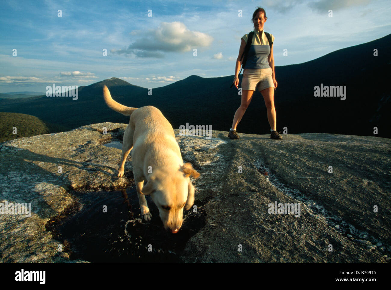 A woman and a dog on a mountain top, Newry, Maine. - Stock Image