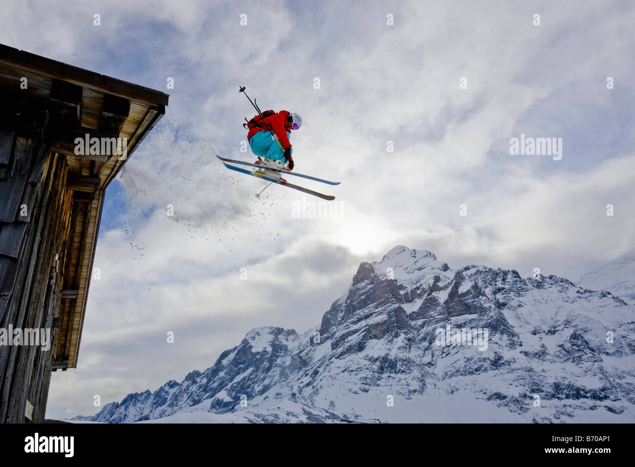 A young man skis off the roof of an alpine hut in Grindalwald, Switzerland. - Stock Image