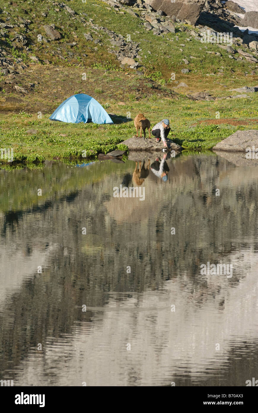 Woman getting water from Clear Lake, San Juan National Forest, Colorado. - Stock Image