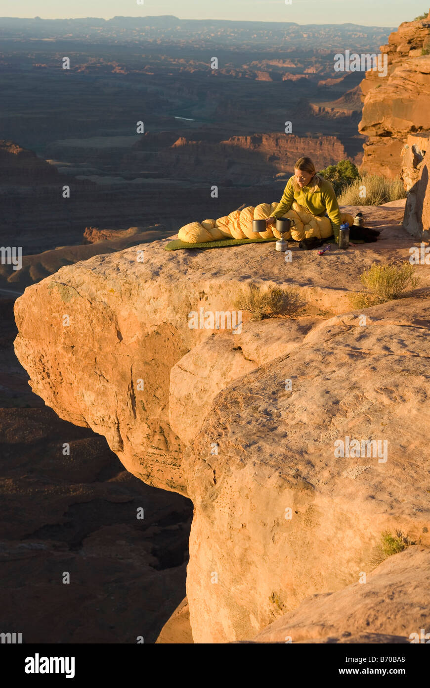 Woman camping on sandstone point, Canyonlands National Park, Utah. - Stock Image