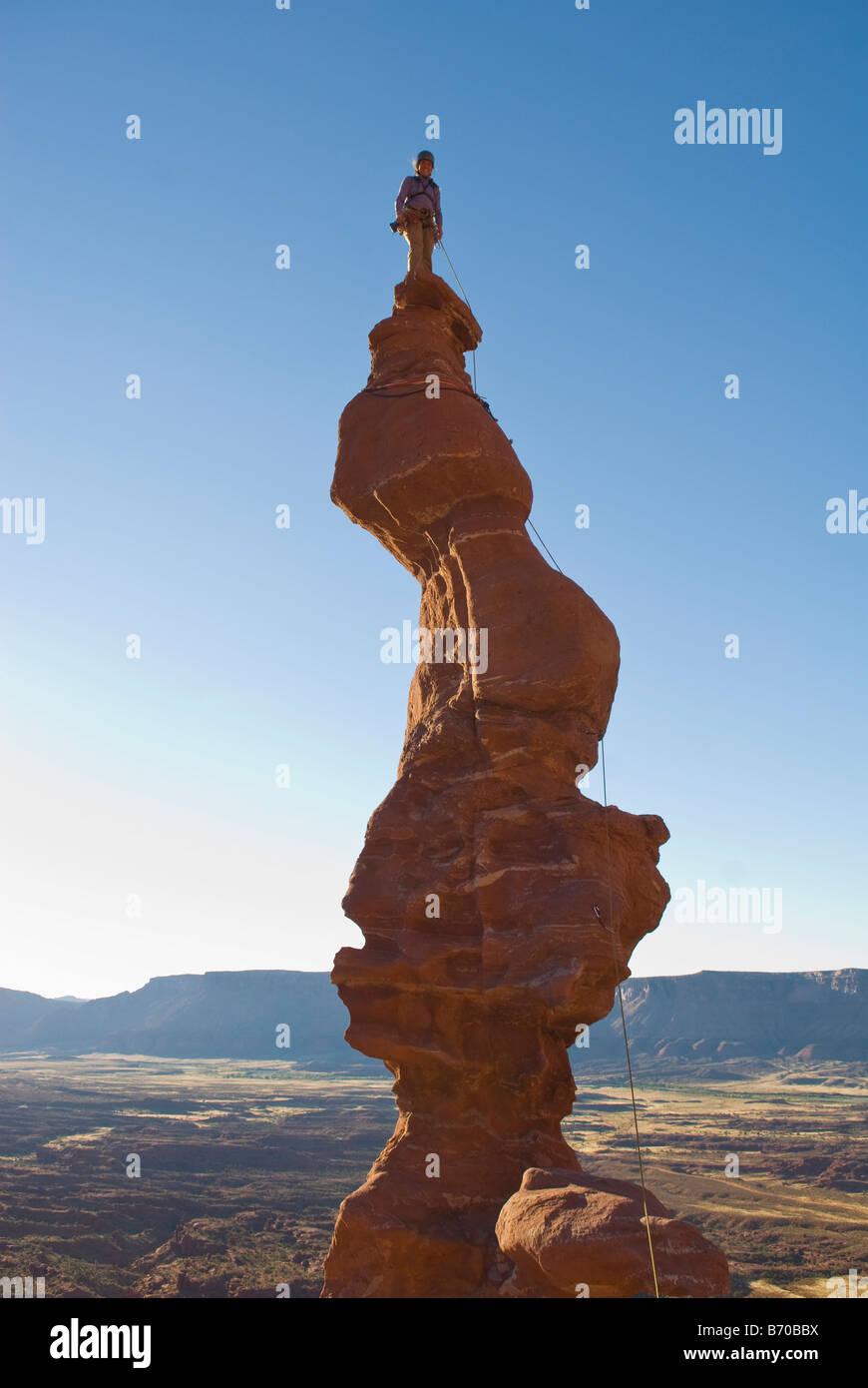 Woman of top of sandstone spire, Fisher Towers, Utah. - Stock Image