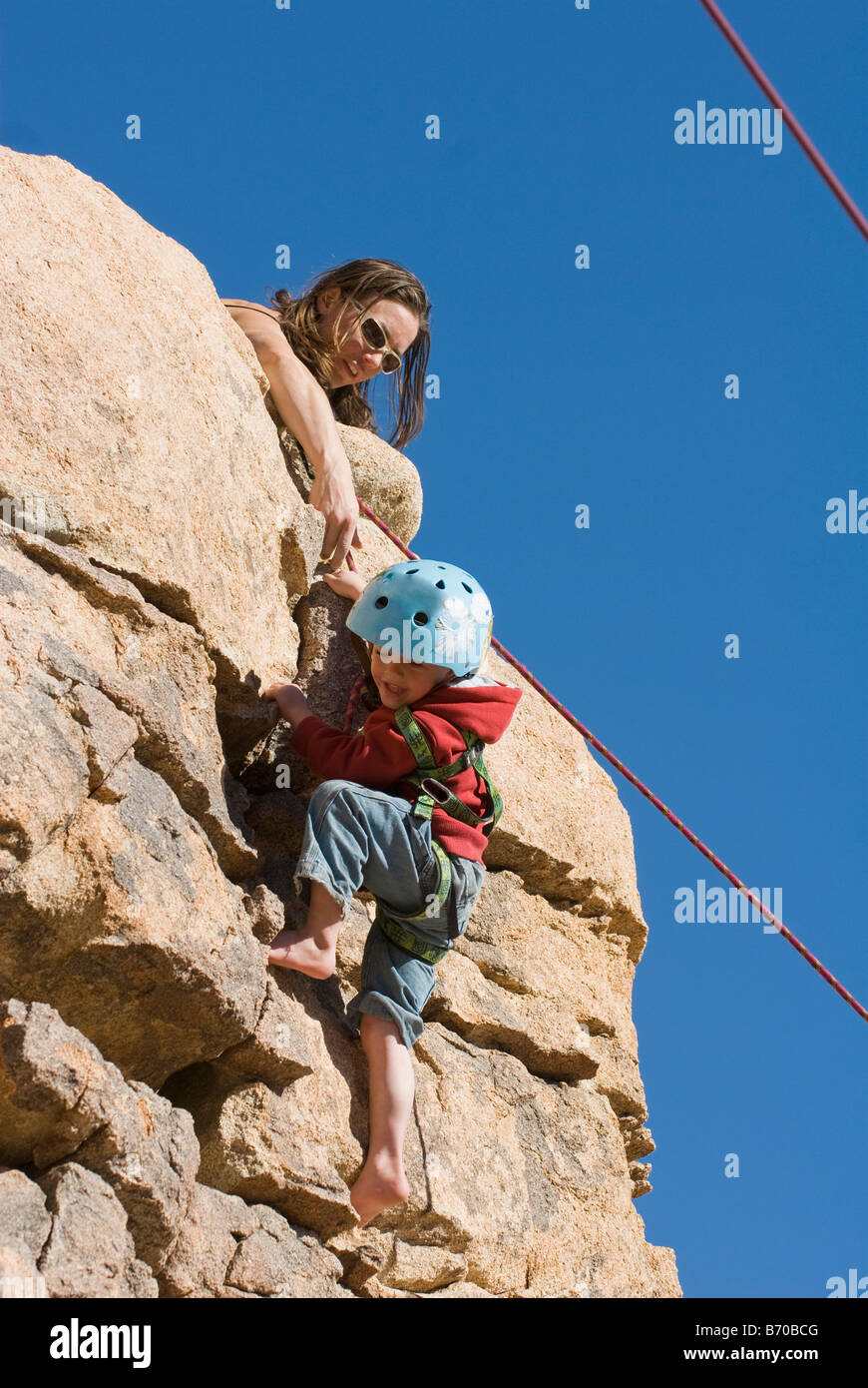 Mother helping child finish a rock climb, Joshua Tree National Park, California. - Stock Image