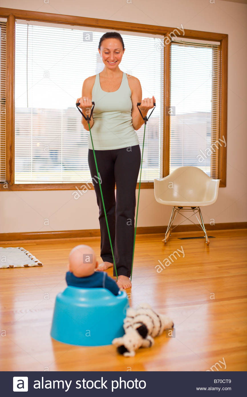 A mother exercises in her home while her baby looks on in Portland, Oregon. - Stock Image