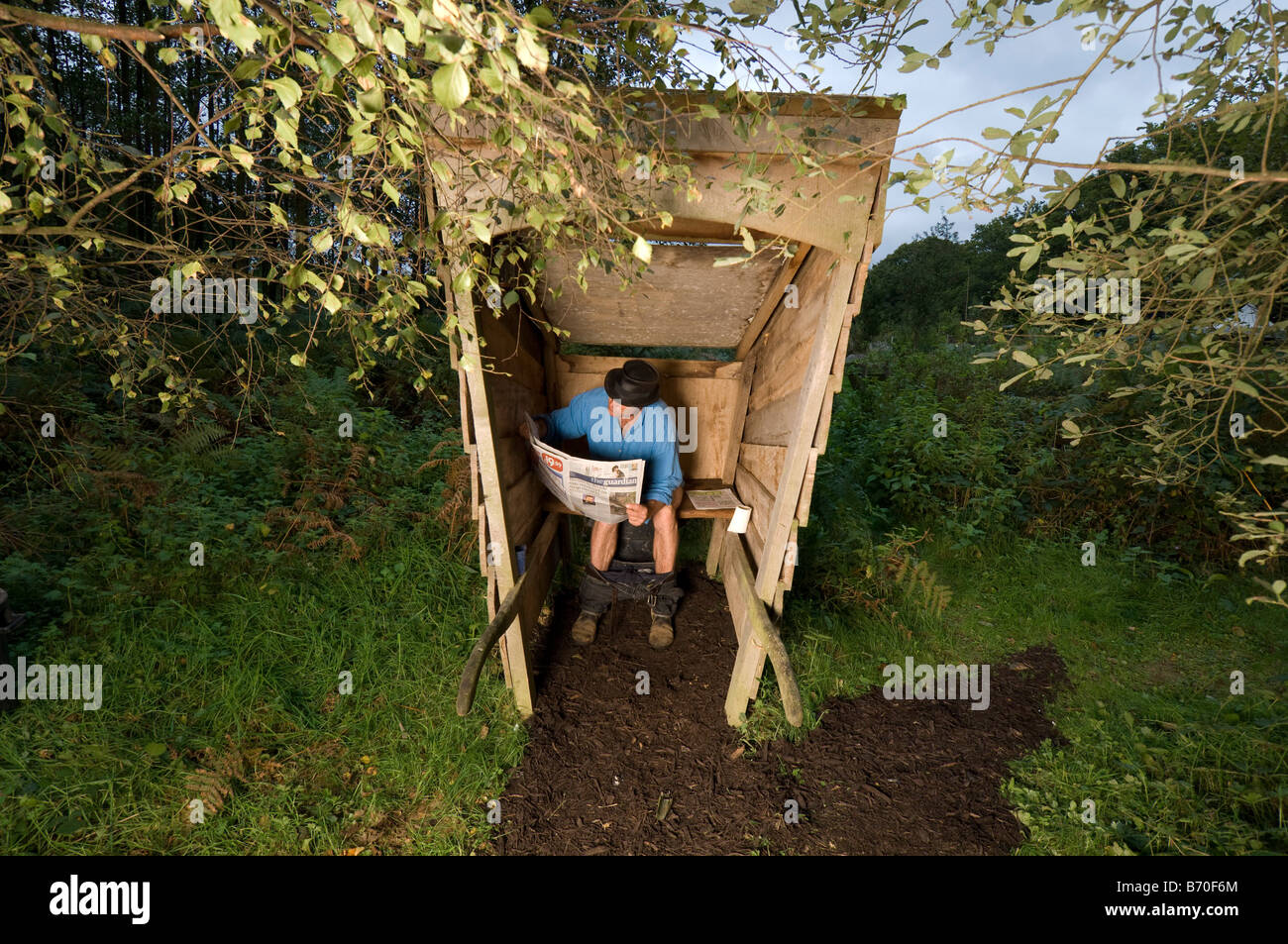 Man reading the Guardian in an outside toilet - Stock Image