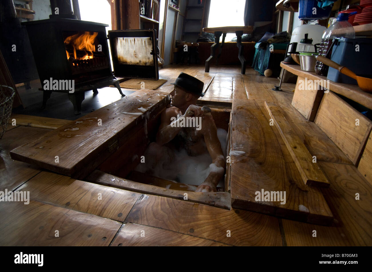 Man Bathing In His Hand Made Wood Cabin Where Bath Is Set Under The Kitchen  Floor And Water Heated On Wood Fired Stove.