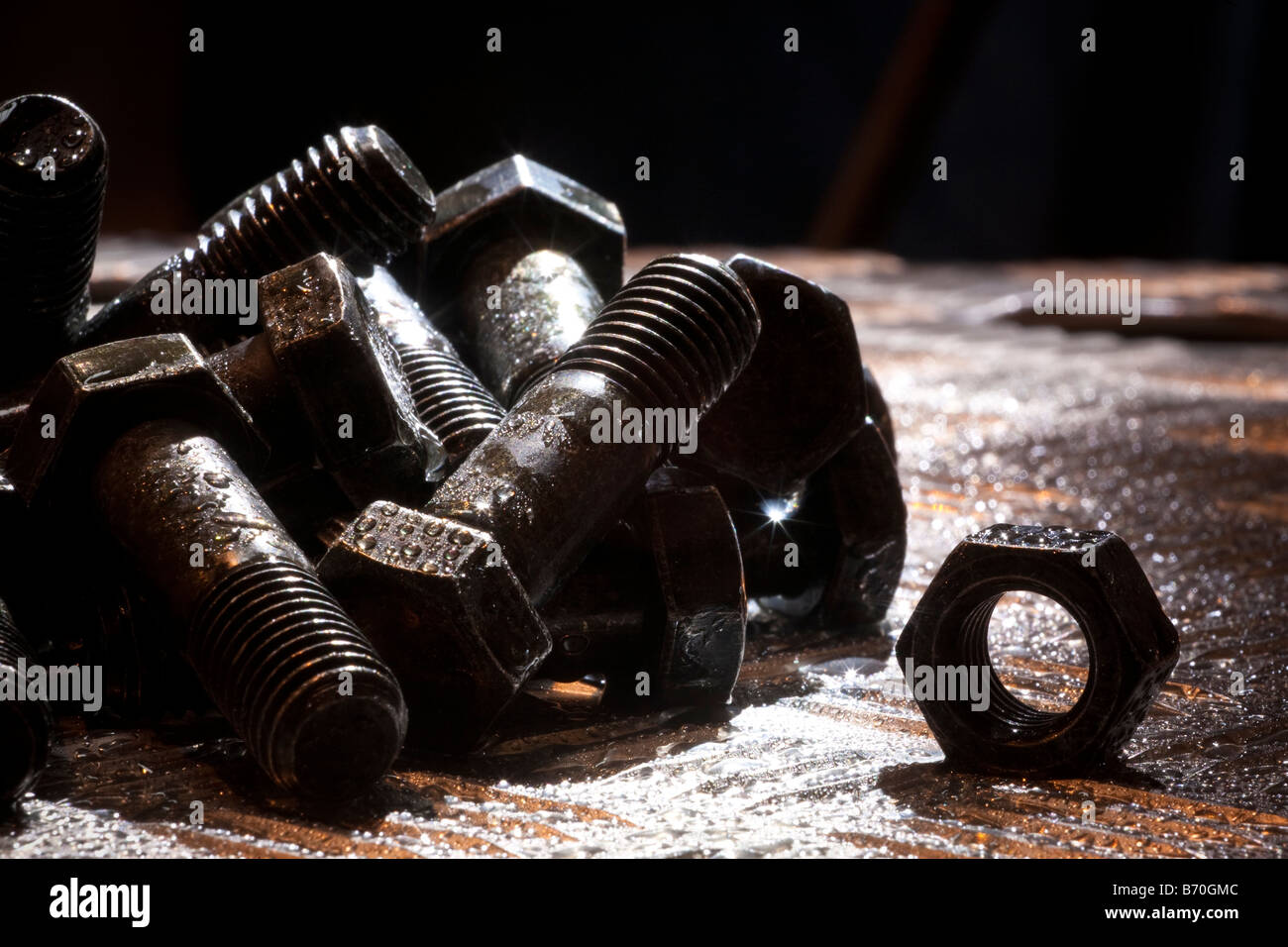 Random artistic pile of threaded bolts and a  hexagonal nut on a sheet steel, backlit, Nut, bolt, steel, sheet, - Stock Image