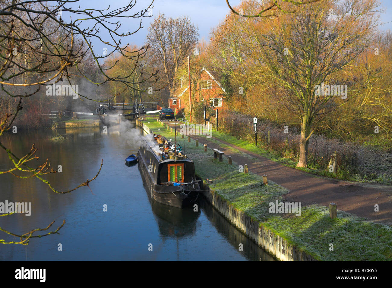 Narrowboat with smoking chimney on a cold winters morning. - Stock Image