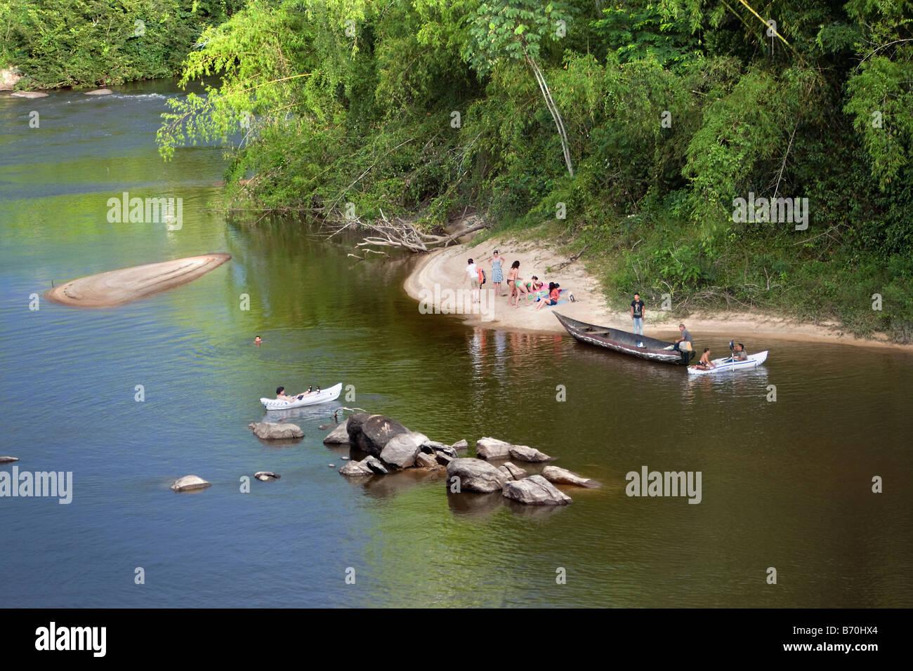 Suriname, Kwamalasamutu, Tourists swimming and kayaking in Sipaliwini river near lodge called Iwana Samu. - Stock Image