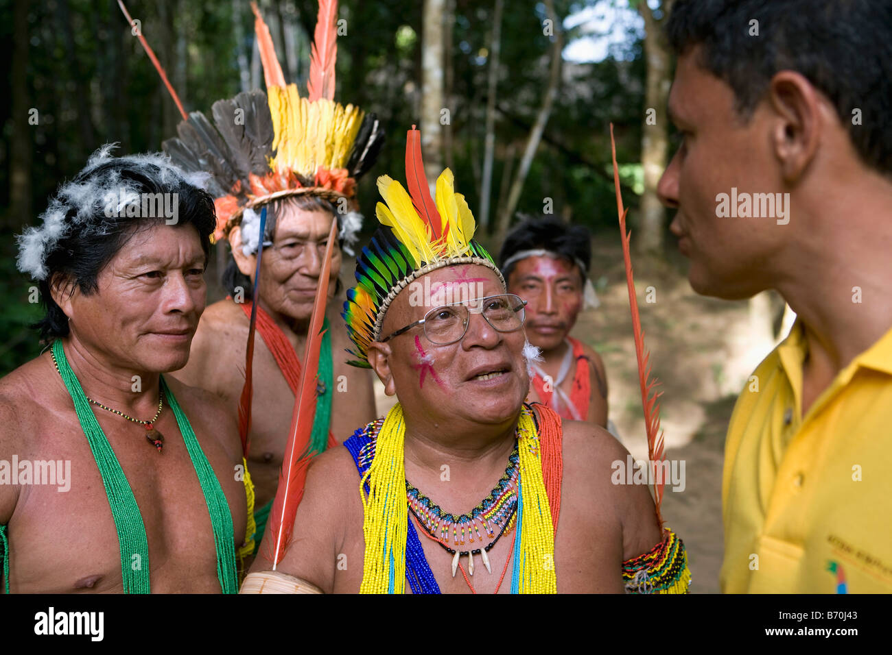 Suriname, Kwamalasamutu, Trio Indians in ceremonial dress talking with tourist guide. Stock Photo