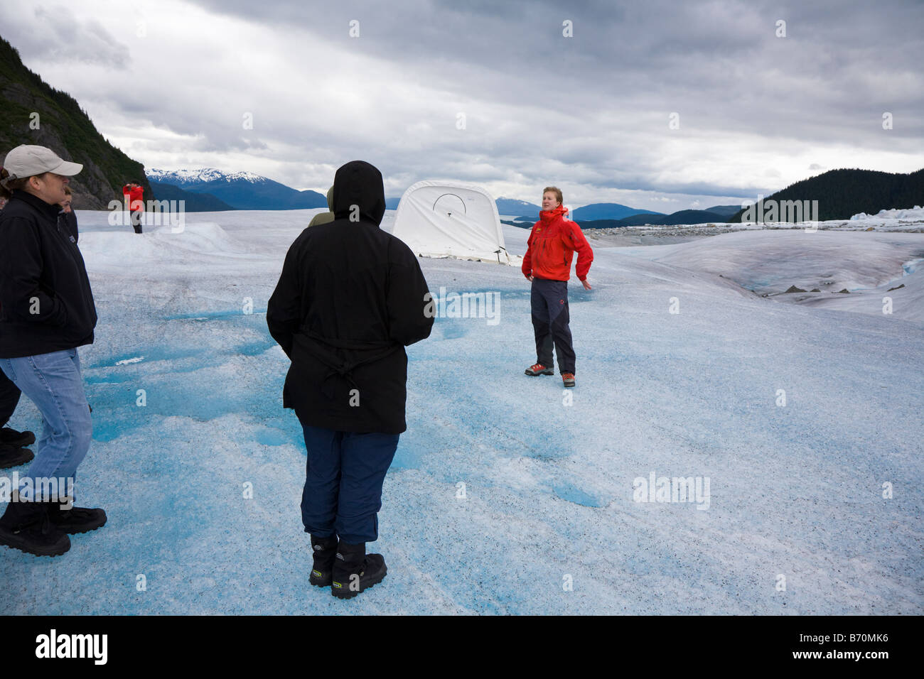 Tour guides at base camp on top of Mendenhall Glacier near Juneau Alaska teach and entertain tourists. - Stock Image