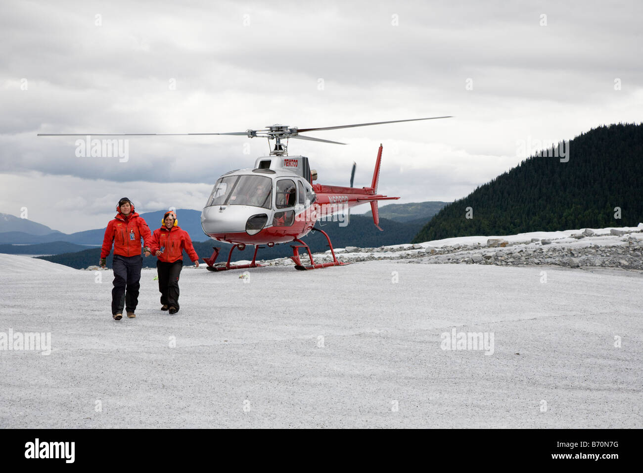 Helicopter tour guides walk from helicopter on top of Mendenhall Glacier near Juneau, Alaska - Stock Image